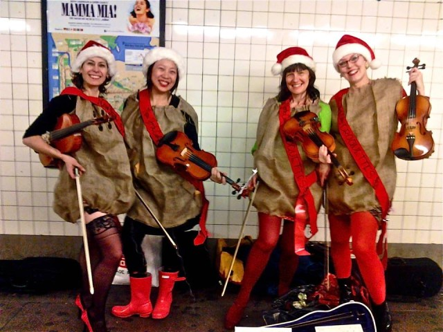 Women playing the violin dressed like Santa