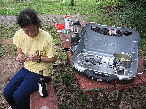 Woman opening bottle of wine while camping