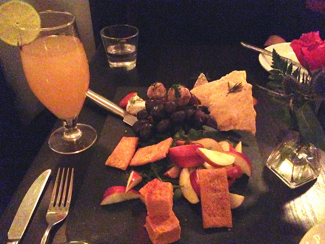 Vegan cheese plate with fruit, cocktail, and flower