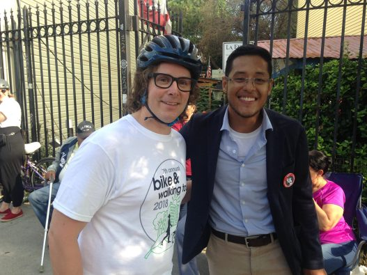 Guy in bike helmet and glasses next to guy in blazer